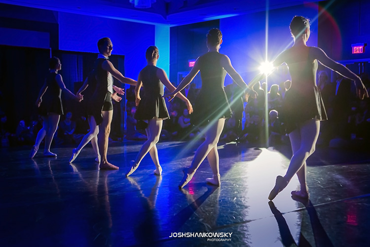 silhouettes of ballerina dancers amongsts blue ambient light.