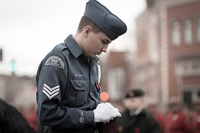 An Air Cadet bows his head during a remebrance day ceremony.