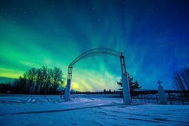 Northern lights casacade through the skin shining through a church gate.